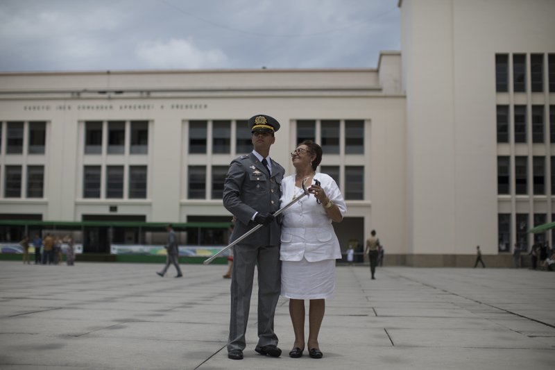 In this Dec. 1, 2018 photo, a Brazilian Army cadet poses with a relative after his graduation ceremony at the Agulhas Negras Military Academy in Resende, Brazil. (AP Photo/Leo Correa)