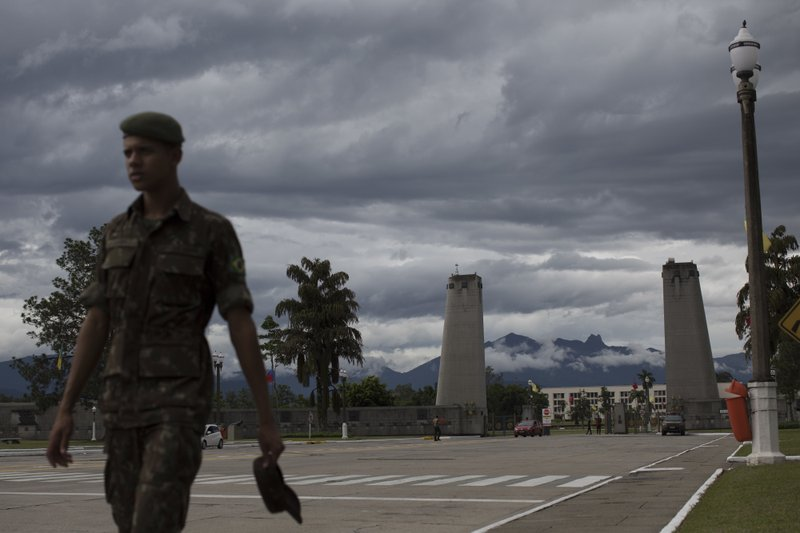 In this Dec. 1, 2018 photo, a Brazilian soldier walks near the entrance of the Agulhas Negras Military Academy in Resende, Brazil. (AP Photo/Leo Correa)