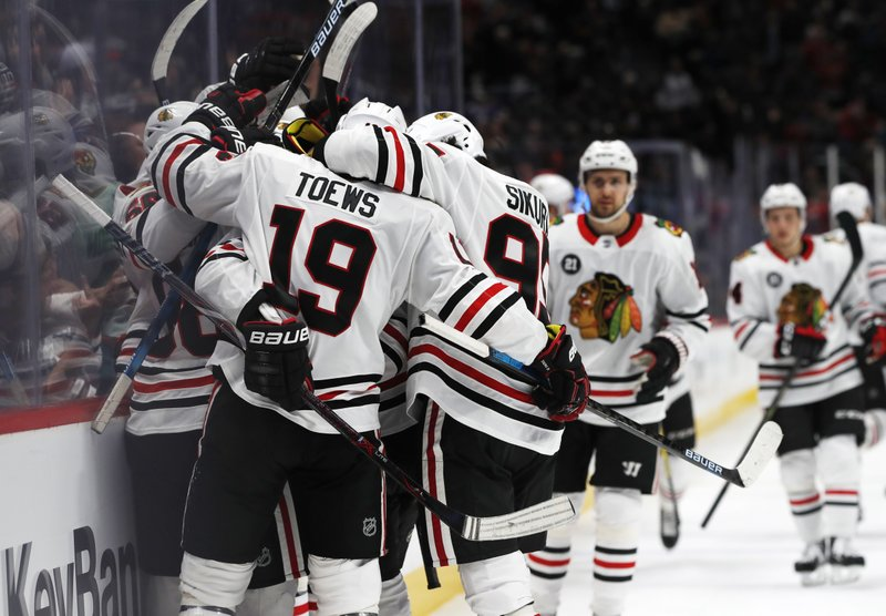 Chicago Blackhawks right wing Patrick Kane is enveloped by teammates, including Jonathan Toews and Dylan Sikura, after Kane scored in overtime of an NHL hockey game Saturday, Dec. (AP Photo/David Zalubowski)