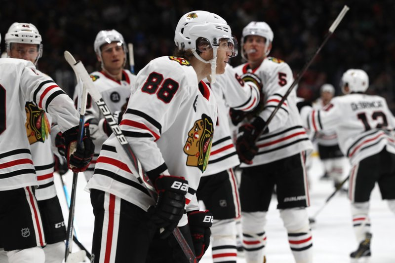 Teammates head to Chicago Blackhawks right wing Patrick Kane (88) after he scored against the Colorado Avalanche in overtime of an NHL hockey game Saturday, Dec. (AP Photo/David Zalubowski)