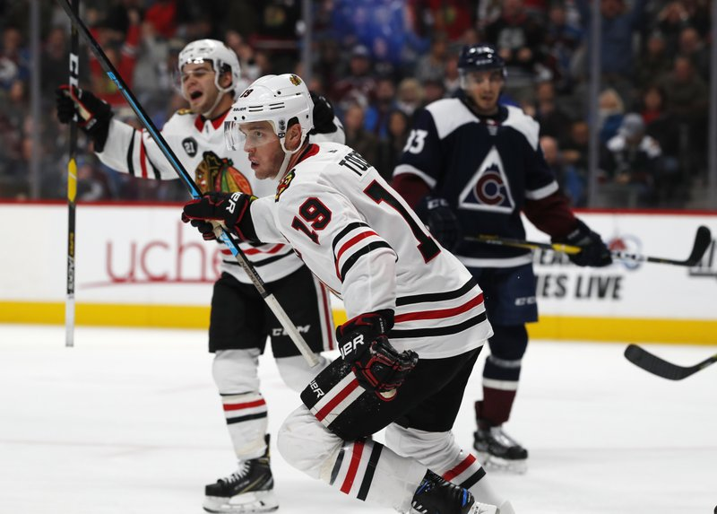Chicago Blackhawks center Jonathan Toews, front, joins left wing Alex DeBrincat, back left, in celebrating after Patrick Kane scored in overtime, as Colorado Avalanche left wing Matt Nieto watches during an NHL hockey game Saturday, Dec. (AP Photo/David Zalubowski)