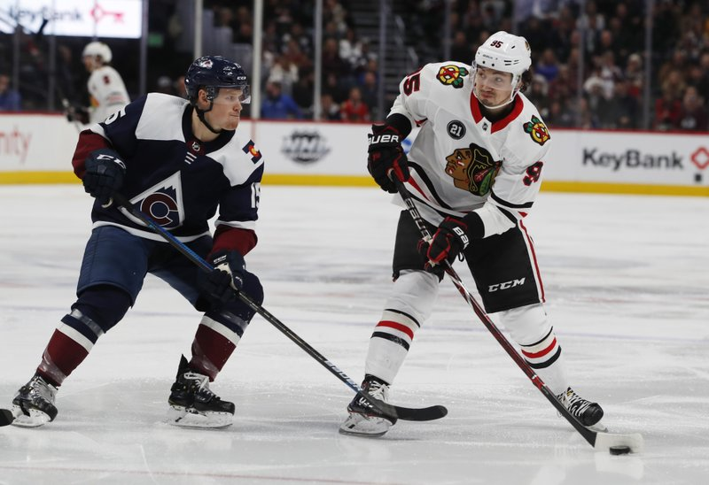 Chicago Blackhawks right wing Dylan Sikura, right, fires the puck at the net past Colorado Avalanche center Sheldon Dries in the second period of an NHL hockey game Saturday, Dec. (AP Photo/David Zalubowski)