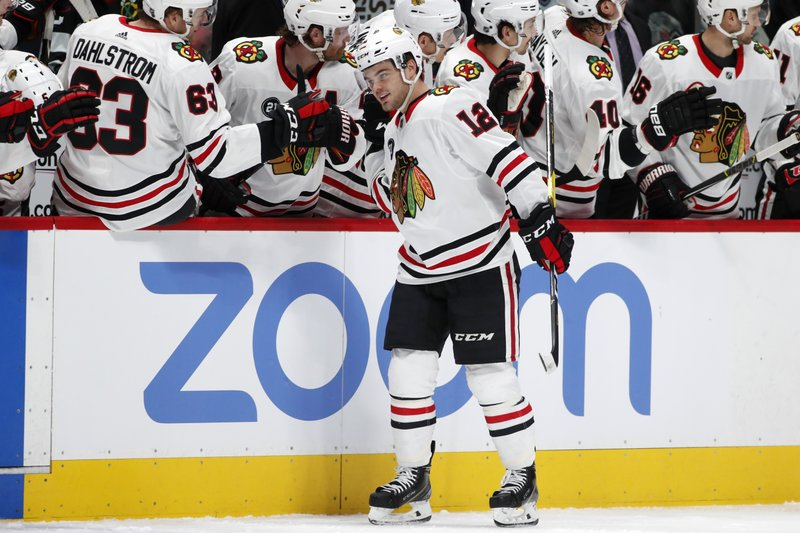 Chicago Blackhawks left wing Alex DeBrincat, front, is congratulated as he passes the team box after scoring a goal against the Colorado Avalanche in the first period of an NHL hockey game Saturday, Dec. (AP Photo/David Zalubowski)