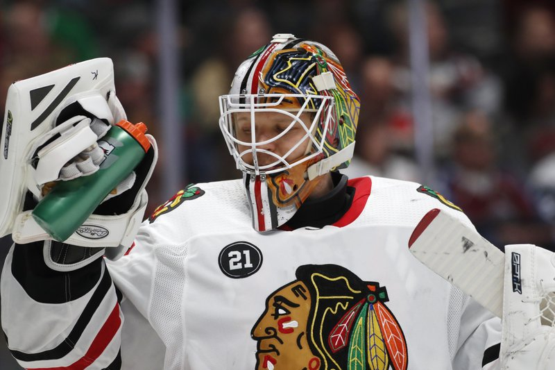 Chicago Blackhawks goaltender Collin Delia takes a drink during a timeout again the Colorado Avalanche in the first period of an NHL hockey game Saturday, Dec. (AP Photo/David Zalubowski)