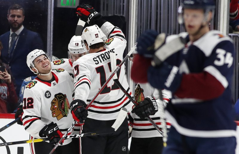 Chicago Blackhawks left wing Alex DeBrincat, left, is congratulated after scoring a goal by centers Jonathan Toews, back right, and Dylan Strome in the first period of an NHL hockey game against the Colorado Avalanche, Saturday, Dec. (AP Photo/David Zalubowski)