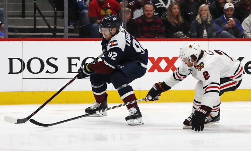Colorado Avalanche left wing Gabriel Landeskog, left, drives past Chicago Blackhawks defenseman Duncan Keith to put a shot on the net in the first period of an NHL hockey game Saturday, Dec. (AP Photo/David Zalubowski)