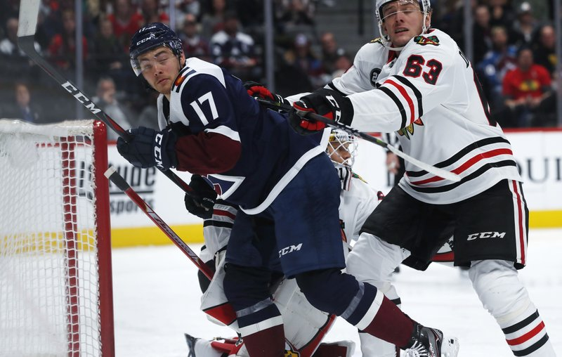 Chicago Blackhawks defenseman Carl Dahlstrom, right, clears Colorado Avalanche center Tyson Jost out from in front of the net in the first period of an NHL hockey game Saturday, Dec. (AP Photo/David Zalubowski)