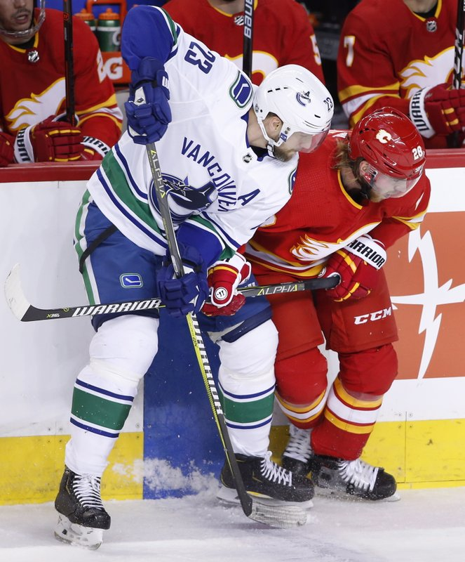 Vancouver Canucks' Alexander Edler, left, from Sweden, battles with Calgary Flames' Elias Lindholm, from Sweden, during the first period of an NHL hockey game Saturday, Dec. (Larry MacDougal/The Canadian Press via AP)