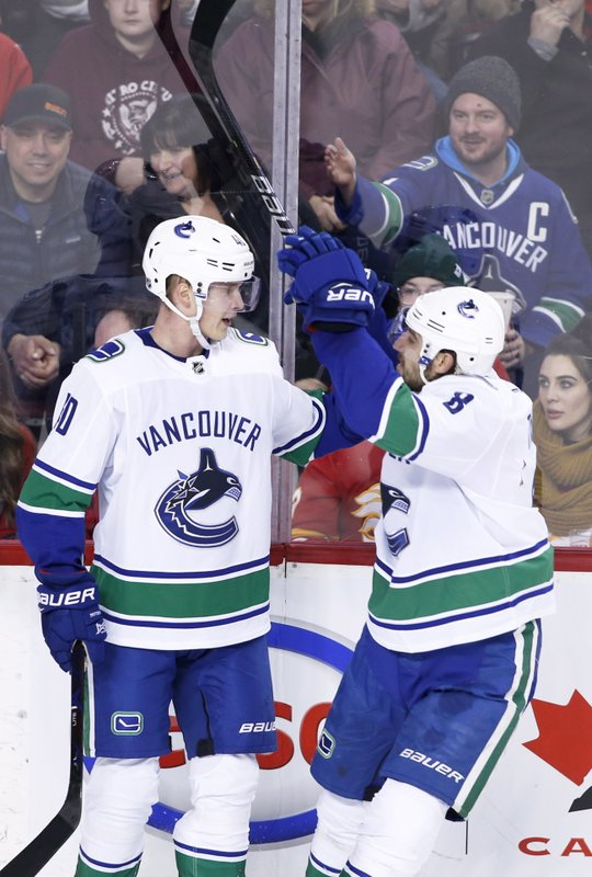 Vancouver Canucks' Elias Pettersson, left, celebrates his goal against the Calgary Flames with Christopher Tanev during the second period of an NHL hockey game Saturday, Dec. (Larry MacDougal/The Canadian Press via AP)