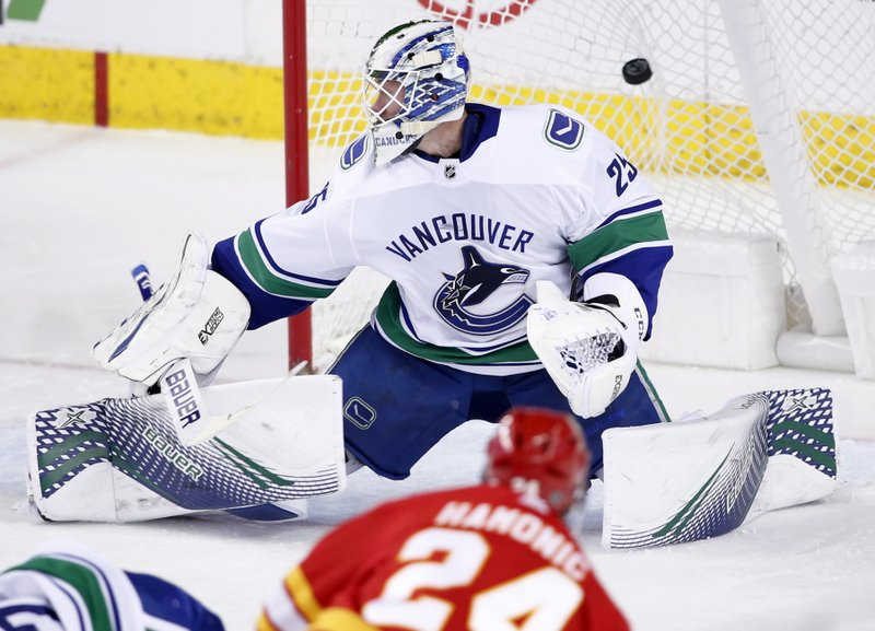 Vancouver Canucks goalie Jacob Markstrom, from Sweden, gives up a goal to Calgary Flames' Travis Hamonic during the second period of an NHL hockey game Saturday, Dec. (Larry MacDougal/The Canadian Press via AP)
