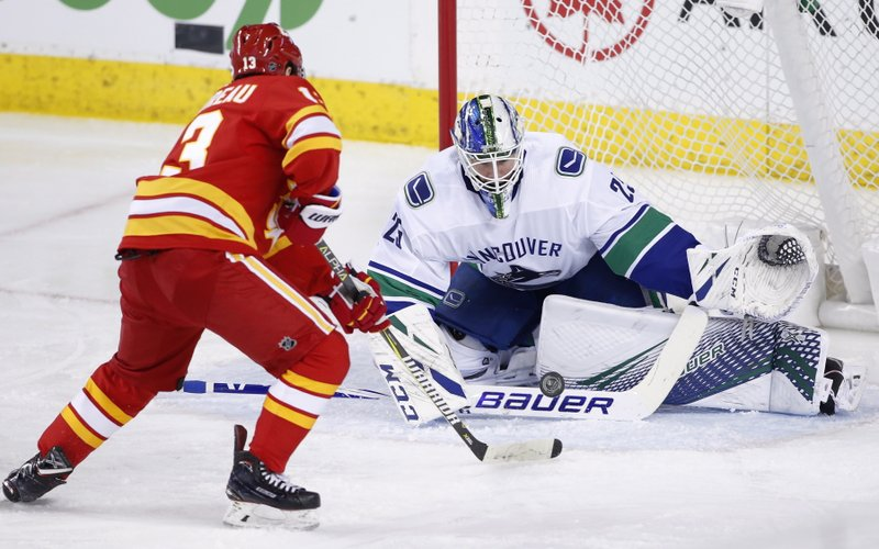 Vancouver Canucks goalie Jacob Markstrom, from Sweden, makes a save against Calgary Flames' Johnny Gaudreau during the second period of an NHL hockey game Saturday, Dec. (Larry MacDougal/The Canadian Press via AP)