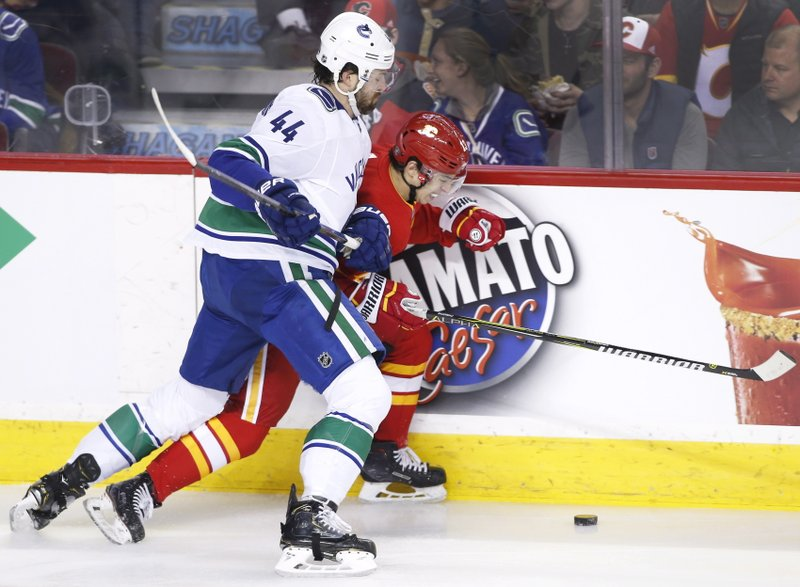 Vancouver Canucks' Erik Gudbranson, left, battles for the puck with Calgary Flames' Johnny Gaudreau during the first period of an NHL hockey game Saturday, Dec. (Larry MacDougal/The Canadian Press via AP)