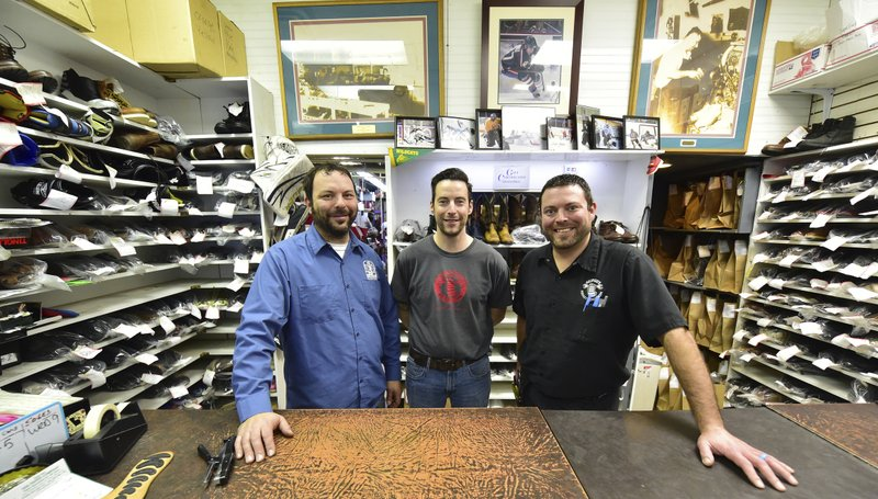 Brothers, from left, Brian, Chris and Dan George at the counter of George's Shoes and Repair on Grand Avenue in St. (John Autey/Pioneer Press via AP)