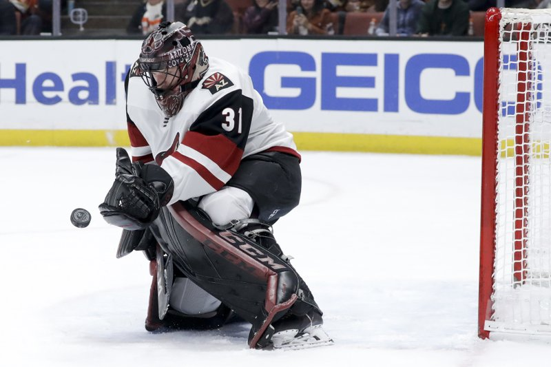 Arizona Coyotes goaltender Adin Hill blocks a shot during the second period of the team's NHL hockey game against the Anaheim Ducks in Anaheim, Calif. (AP Photo/Chris Carlson)