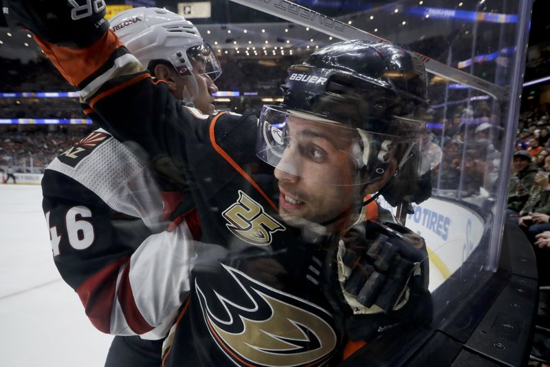 Arizona Coyotes defenseman Ilya Lyubushkin, left, checks Anaheim Ducks left wing Andrew Cogliano into the glass during the second period of an NHL hockey game in Anaheim, Calif. (AP Photo/Chris Carlson)