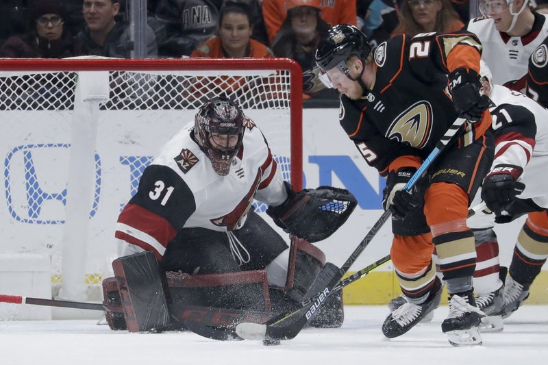 Arizona Coyotes goaltender Adin Hill, left, blocks a shot by Anaheim Ducks right wing Ondrej Kase during the first period of an NHL hockey game in Anaheim, Calif. (AP Photo/Chris Carlson)