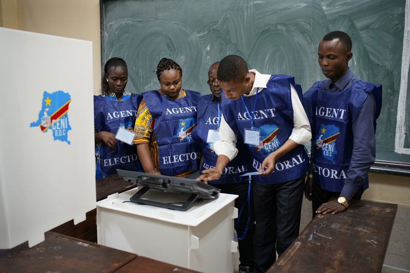 Congolese election officials get the voting machine ready before voting starts Sunday, Dec. 30, 2018 in Kinshasa, Congo. (AP Photo/Jerome Delay)