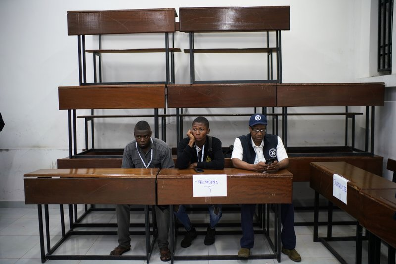 Election observers sit in a polling stating as voters cast their vote Sunday, Dec. 30, 2018 in Kinshasa, Congo. (AP Photo/Jerome Delay)