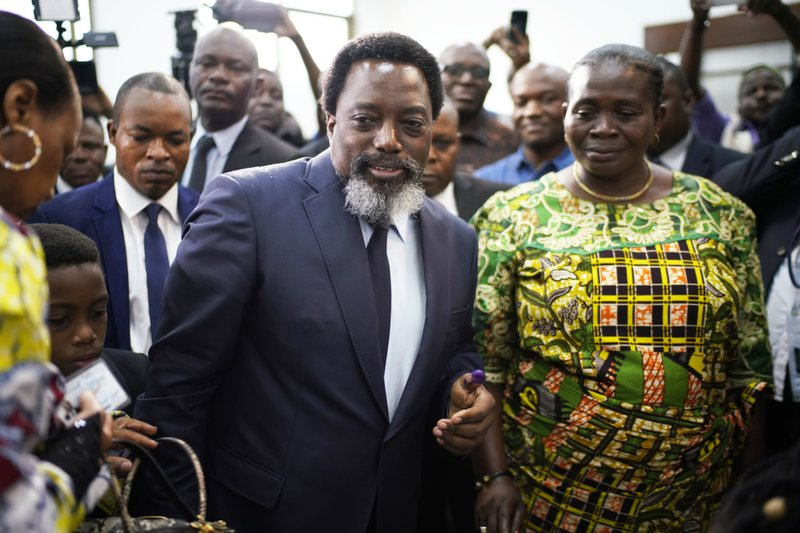 Congolese President Joseph Kabila, center, leaves the polling station after casting his vote Sunday Dec. (AP Photo/Jerome Delay)