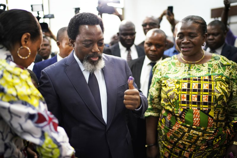 Congolese President Joseph Kabila, center, leaves the polling station after casting his vote Sunday, Dec. (AP Photo/Jerome Delay)