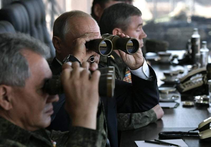 FILE In this file photo taken on Thursday, Sept. 13, 2018, Russian President Vladimir Putin, center, holds binoculars while watching a military exercises on training ground