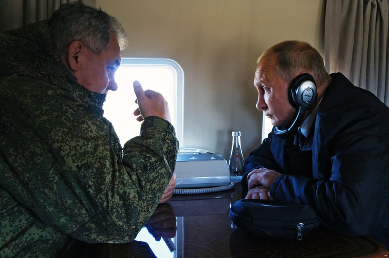 FILE In this file photo taken on Thursday, Sept. 13, 2018, Russian President Vladimir Putin, right, listens to Russian Defense Minister Sergei Shoigu on a board of military helicopter during their flight to attend a military exercises on training ground
