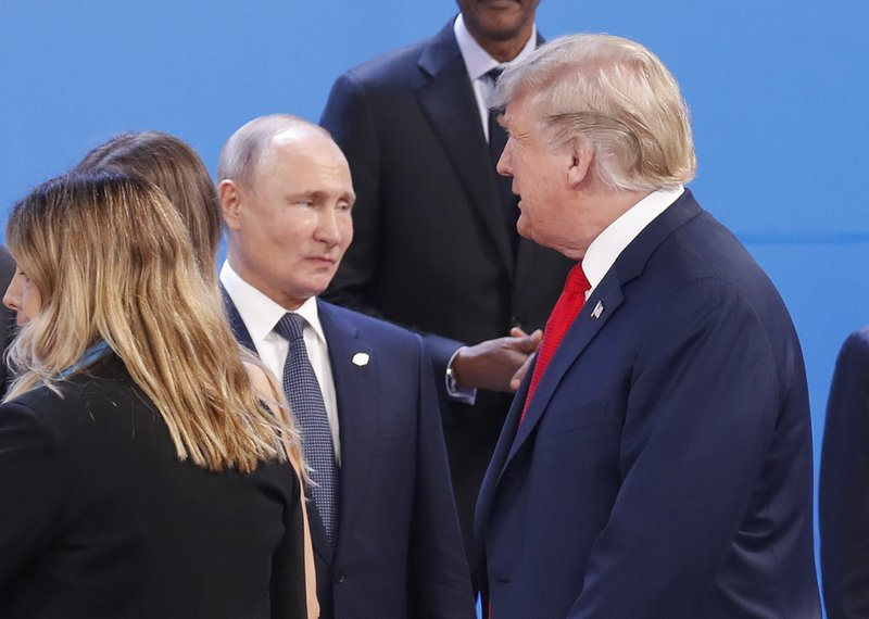 FILE - In this Nov. 30, 2018, file photo, President Donald Trump, right, walk past Russia's President Vladimir Putin, left, as they gather for the group photo at the start of the G20 summit in Buenos Aires, Argentina. ( (AP Photo/Pablo Martinez Monsivais, File)