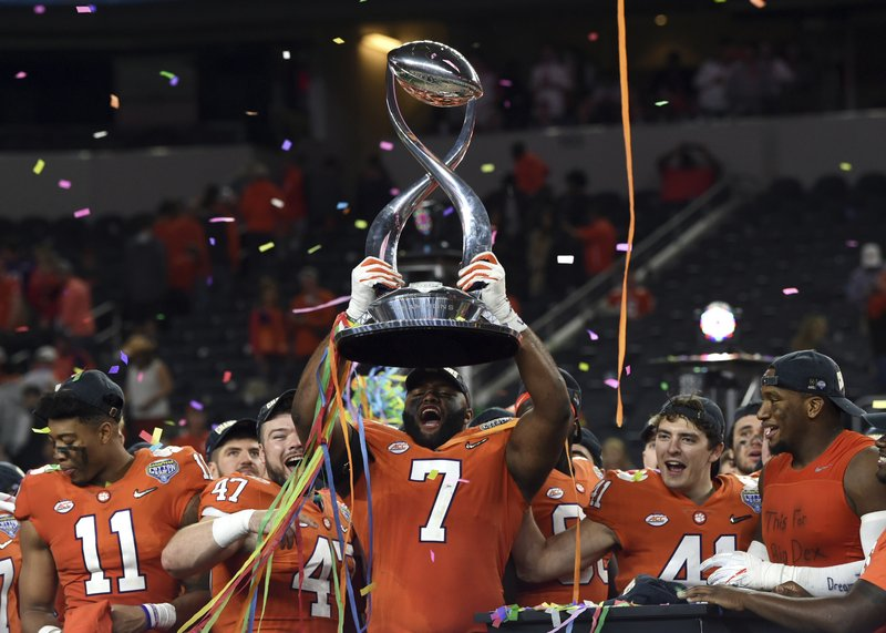 Clemson defensive end Austin Bryant (7) holds up the trophy as the team celebrates their 30-3 win against Notre Dame in the NCAA Cotton Bowl semi-final playoff football game, Saturday, Dec. (AP Photo/Jeffrey McWhorter)