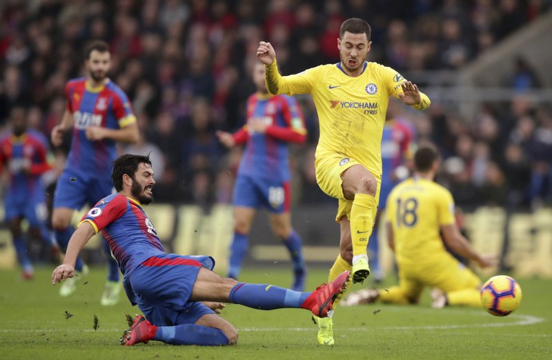 Chelsea's Eden Hazard is challenged by Crystal Palace's James Tomkins, left, during their English Premier League soccer match at Selhurst Park in London, Sunday Dec. (John Walton/PA via AP)