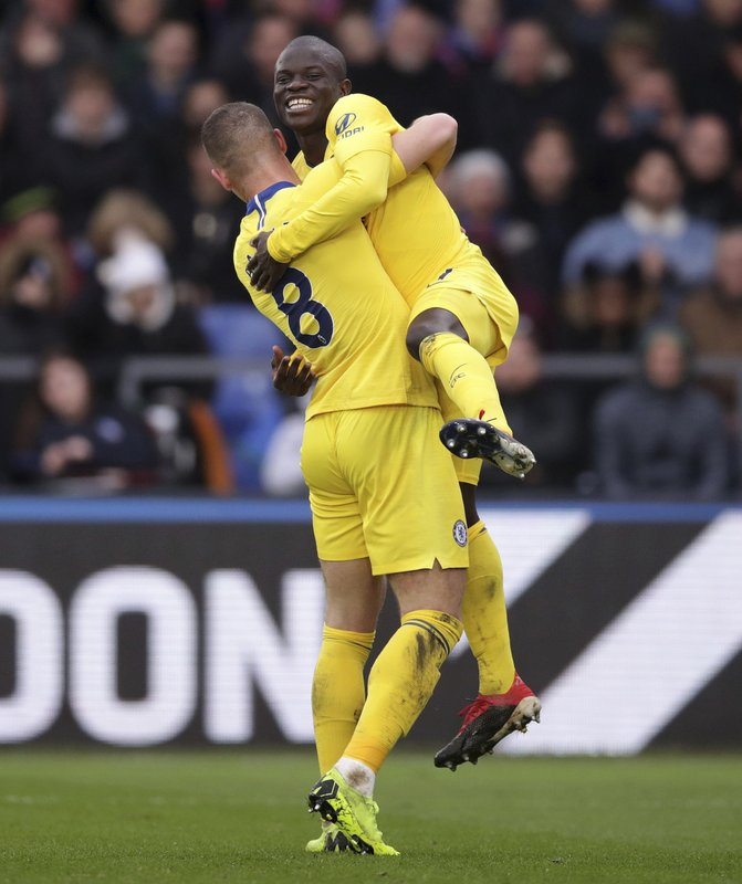 Chelsea's N'Golo Kante, top, celebrates scoring his side's first goal of the game against Crystal Palace, with teammate Ross Barkley, during their English Premier League soccer match at Selhurst Park in London, Sunday Dec. (John Walton/PA via AP)