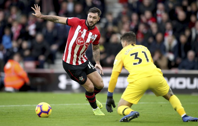 Southampton's Charlie Austin, left, tries to reach the ball ahead of Manchester City goalkeeper Ederson, during their English Premier League soccer match at St Mary's Stadium in Southampton, England, Sunday Dec. (Adam Davy/PA via AP)