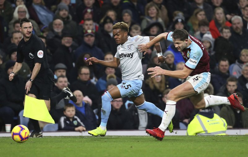 West Ham United's Grady Diangana and Burnley's James Tarkowski, right, during their English Premier League soccer match at Turf Moor in Burnley, England, Sunday Dec. (Richard Sellers/PA via AP)