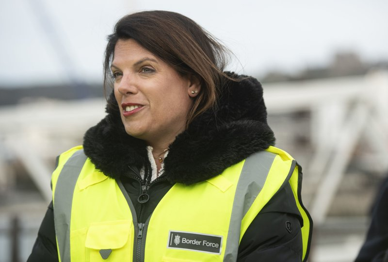 Britain's Immigration Minister Caroline Nokes talks to a Border Force officer in the harbour of Dover, England, to discuss recent attempts by migrants to reach Britain by small boats, Saturday Dec. (Victoria Jones/PA via AP)