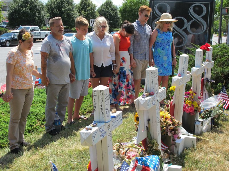 FILE - In this file photo dated Thursday, July 5, 2018, people pause for a moment of silence next to a memorial near the Capital Gazette building, in Annapolis, Md. (AP Photo/Brian Witte, FILE)
