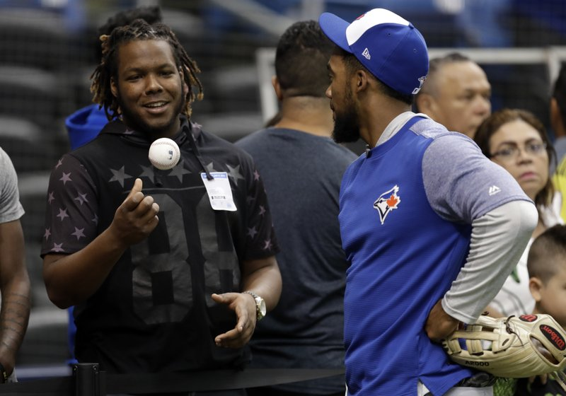 File-This June 11, 2018, file photo shows Toronto Blue Jays prospect Vlad Guerrero Jr., left, talking to right fielder Teoscar Hernandez before a baseball game  in St. (AP Photo/Chris O'Meara, File)