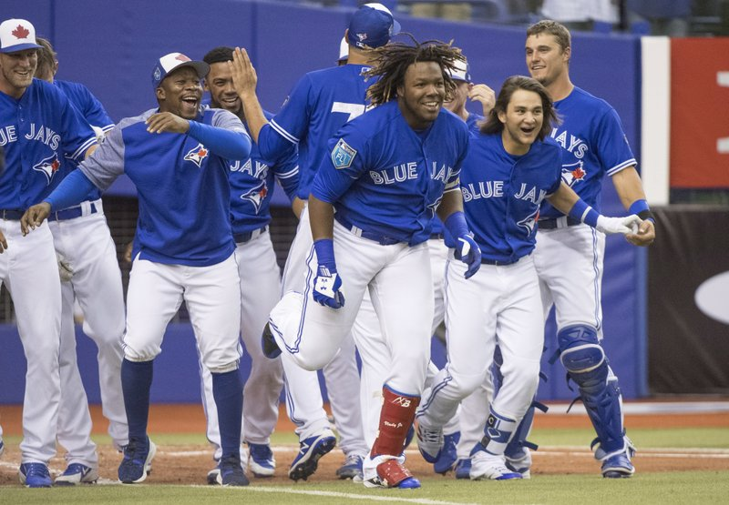 FILE - In this March 27, 2018, file photo, Toronto Blue Jays' Vladimir Guerrero Jr., center, and teammates celebrate his home run against the St. (Paul Chiasson/The Canadian Press via AP, File)