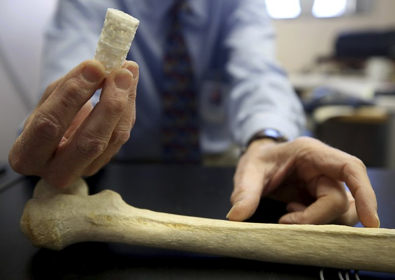 In this Dec. 17, 2018 photo, John Szivek, Rubin chair in orthopedic research professor at the University of Arizona, holds a scaffold and explains how it can help to regrow bone in Tucson, Ariz. (Mamta Popat/Arizona Daily Star via AP)