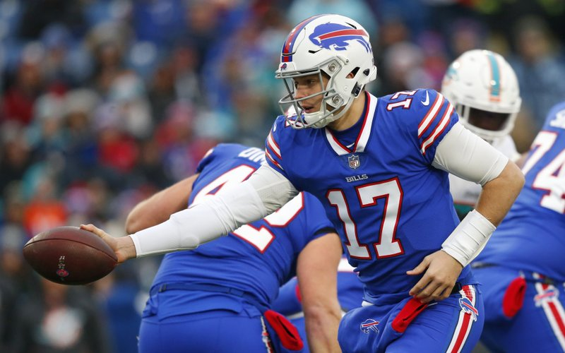 Buffalo Bills quarterback Josh Allen reaches to hand off the ball during the first half of an NFL football game against the Miami Dolphins, Sunday, Dec. (AP Photo/Jeffrey T. Barnes)