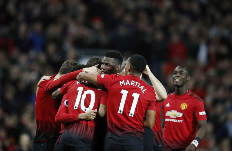 Manchester United's Paul Pogba, centre, celebrates with teammates after scoring his side's first goal of the game against Bournemouth, during their English Premier League soccer match at Old Trafford in Manchester, England, Sunday Dec. (Martin Rickett/PA via AP)