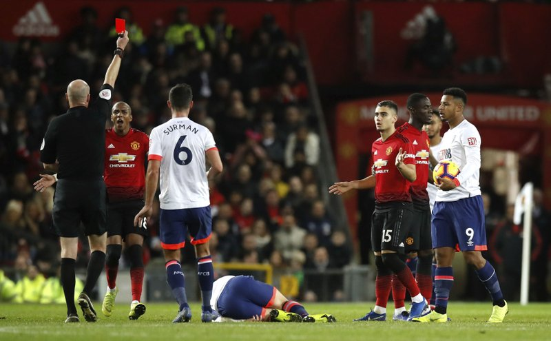 Referee Lee Mason shows a red card to Manchester United's Eric Bailly, second left, for serious foul play during the English Premier League soccer match between Manchester United and AFC Bournemouth at Old Trafford, Manchester, England, Sunday, Dec. (Martin Rickett/PA via AP)