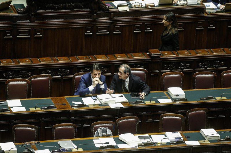 Italian Premier Giuseppe Conte, left, and Economy Minister Giovanni Tria shares word  during the vote of confidence on the budget law at the Italian lower chamber in Rome, Saturday, Dec. (Fabio Frustaci/ANSA via AP)