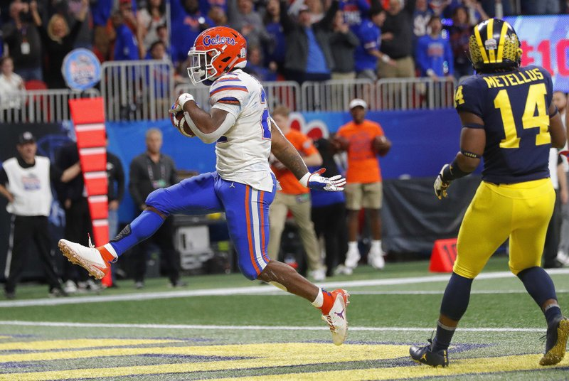 Florida running back Lamical Perine (22) runs into the end zone for a touchdown against Michigan during the first half of the Peach Bowl NCAA college football game, Saturday, Dec. (AP Photo/John Bazemore)
