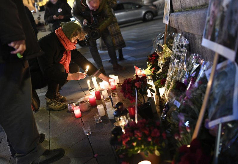 Flowers and candles are placed in memory of two Scandinavian university students who were killed in a remote area of the Atlas Mountains in Morocco, at the Town Hall Square in Copenhagen, Friday Dec. (Thomas Sjoerup / Ritzau Scanpix)