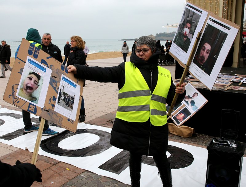 A demonstrator wearing yellow vest holds photos showing who they say are victims of police violence in recent weeks in France, in Biarritz, southwestern France, Sunday, Dec. (AP Photo/Bob Edme)