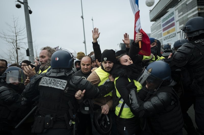 French riot police officers hold back demonstrators wearing yellow vests as they demonstrate in front of the french public television network (France Televisions) in Paris, Saturday, Dec. (AP Photo/Kamil Zihnioglu)