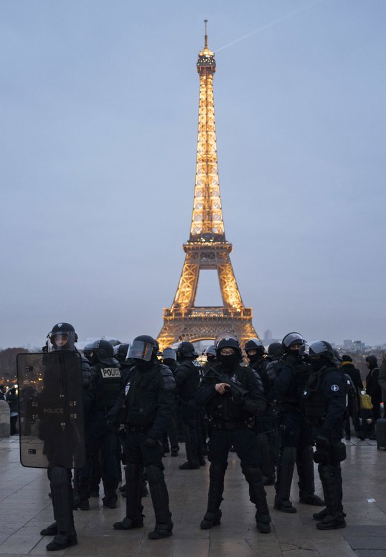 French riot police officers take position on the Trocadero plaza during a demonstration in Paris, Saturday, Dec. (AP Photo/Kamil Zihnioglu)