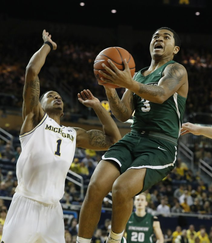Binghamton guard Sam Sessoms (3) makes a layup as Michigan guard Charles Matthews (1) defends during the first half of an NCAA college basketball game, Sunday, Dec. (AP Photo/Carlos Osorio)