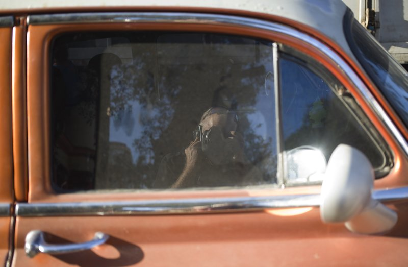 Associated Press photojournalist Desmond Boylan takes a picture of his reflection in a car window as he talks on his cell phone at a market where he was taking pictures of shoppers buying last minute items for their traditional news years dinners at a market in Havana, Cuba, Saturday, Dec. (AP Photo/Desmond Boylan)