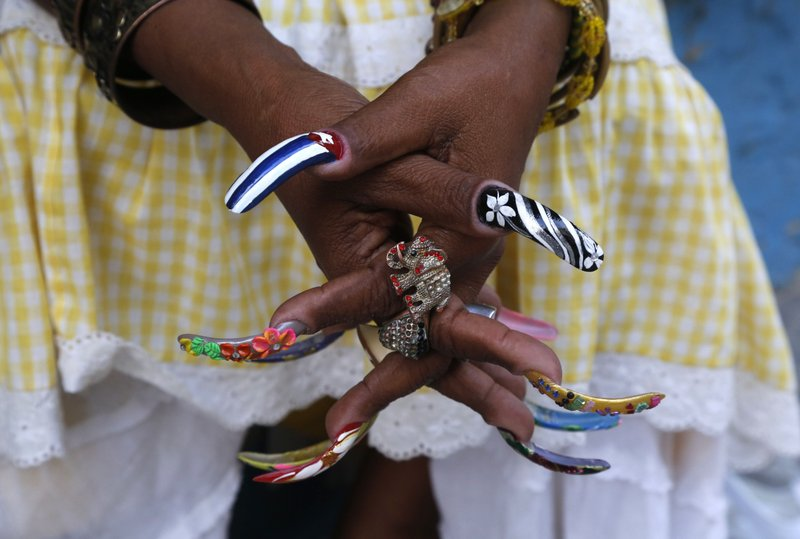 FILE - In this Jan. 15, 2015 file photo, fortune teller Adelaida waits for her nail polish to dry as she sits on the sidewalk in Old Havana, Cuba. (AP Photo/Desmond Boylan, File)