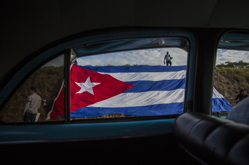 FILE - In this Dec. 2, 2016 file photo, a Cuban flag covers the side of the road where people wait for the funeral procession of Fidel Castro on the outskirts of Las Tunas, Cuba. (AP Photo/Desmond Boylan, File)